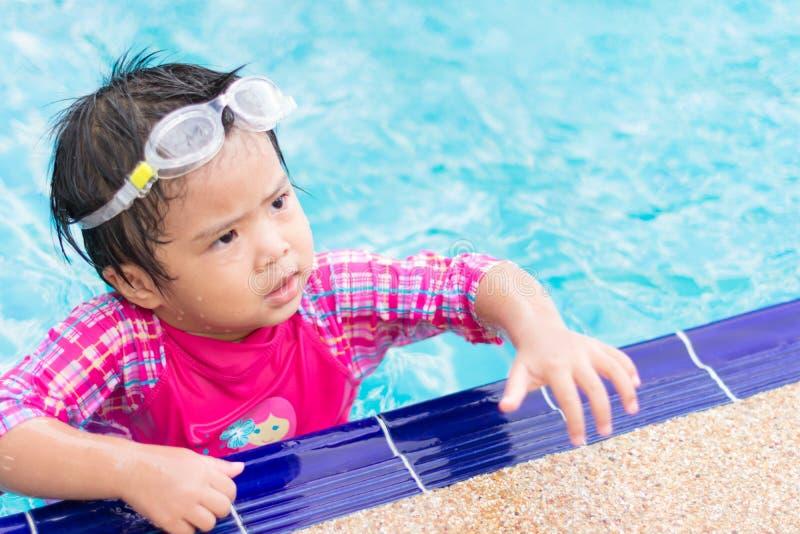 Den lilla asiatiska flickan som bär vattentäta sunglassses, försöker att simma al arkivbild
