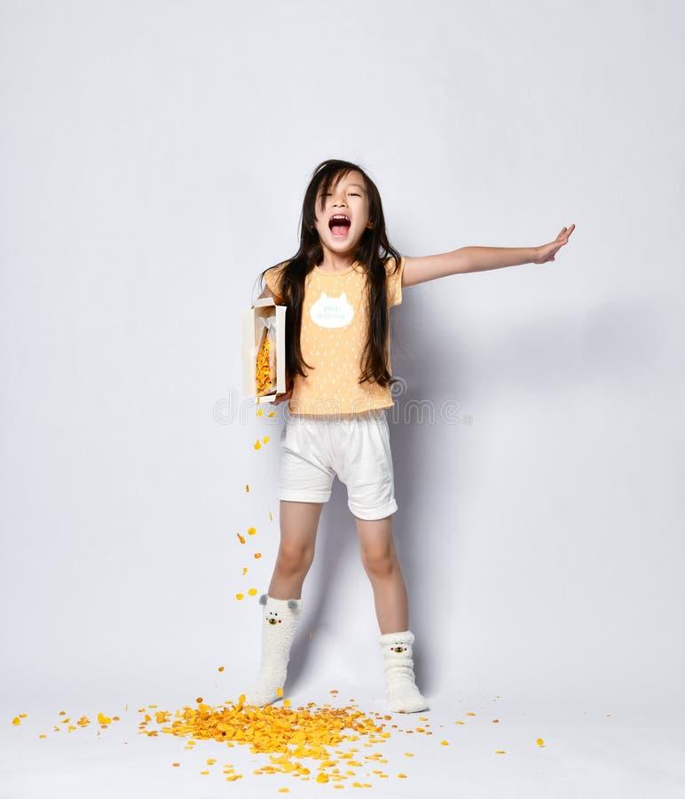 Den lilla asiatiska flickaungen hällde hennes cornflakes frukosterar ut på golvet, medan gira och sträcka på morgonen royaltyfri bild