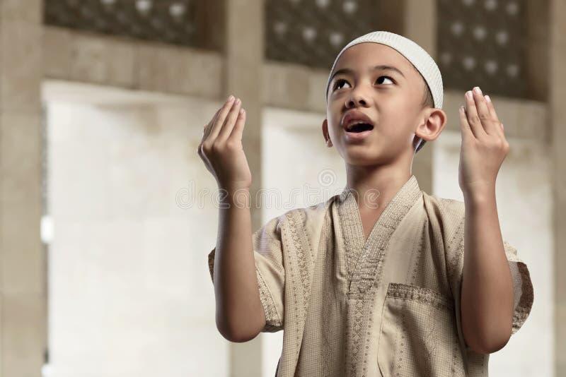 Den lilla asiatiska muslimpojken ber med lönelyfthanden royaltyfri foto