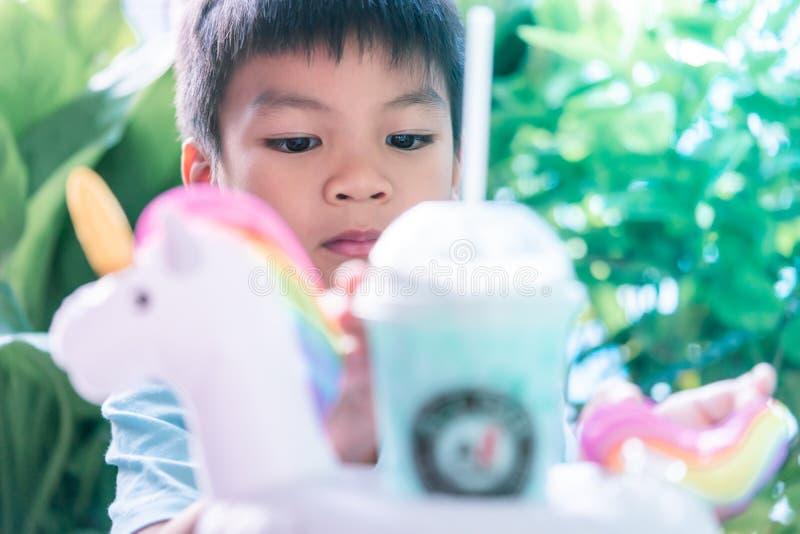 Den lilla asiatiska pojken som dricker enhörningen, mjölkar royaltyfri foto