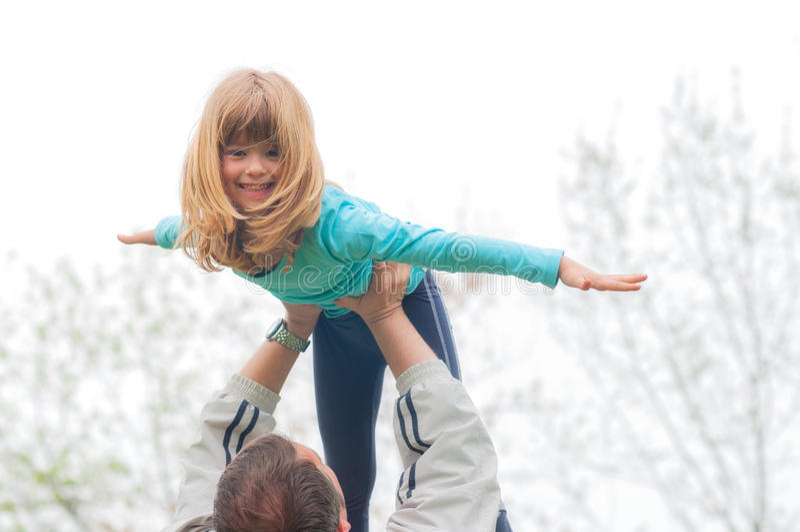 Den lilla blonda flickan lyftte högt i luften av hennes utomhus- fader arkivbilder