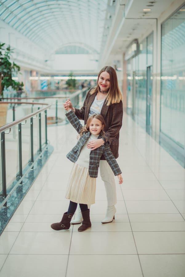 Den lilla blonda flickan med hennes mamma shoppar på gallerian Svart fredag begrepp arkivbilder