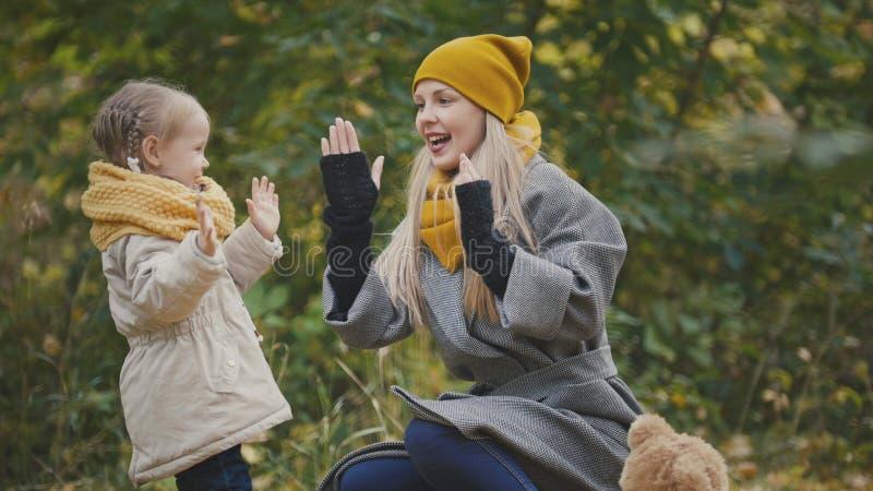 Den lilla blonda flickan med hennes mamma spenderar tid i höst parkerar - lek och applåderar upp händer, slut arkivbild