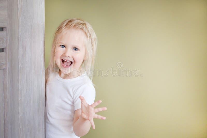 Den lilla blonda flickan med långt hår i enkort vit Flickan i titt bakifrån dörren och ämnar skrämma somebod royaltyfri fotografi