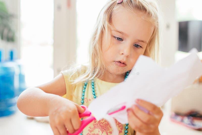 Den lilla blonda flickan med scissor på förträningen Utbildning Ståenden av gulligt behandla som ett barn lite flickan som klippe royaltyfria bilder