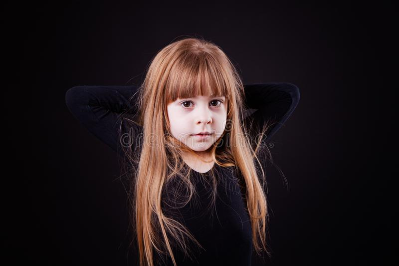 Den lilla blonda flickan rymmer hennes händer bak hennes huvud på svarta lodisar royaltyfri bild
