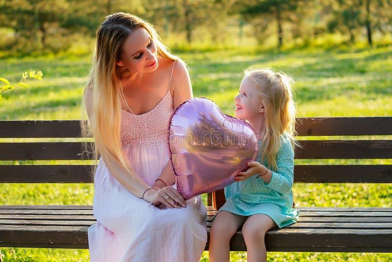 Den lilla blonda flickans dotter i en blå klänning som sitter på en bänk med en vacker mamma som har kul och kul. fotografering för bildbyråer