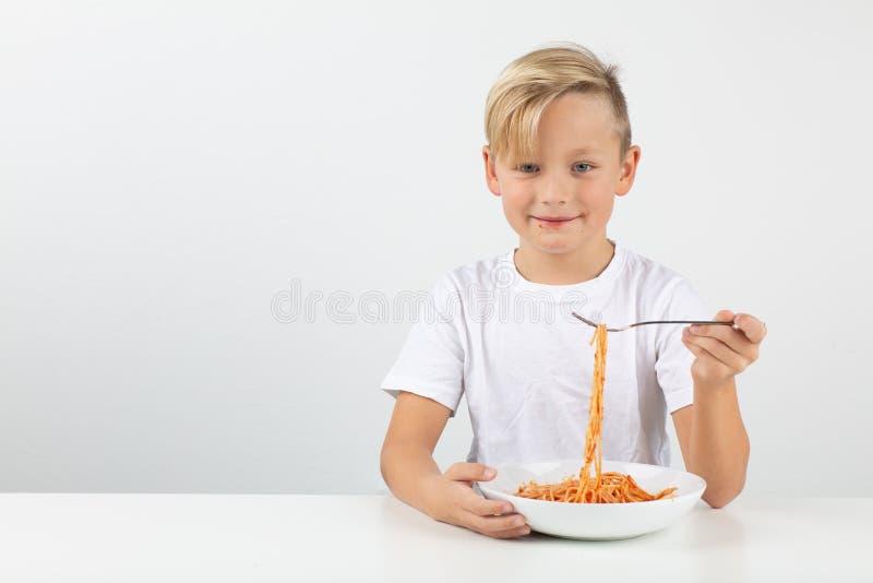Den lilla blonda pojken äter spagetti och leenden royaltyfria foton