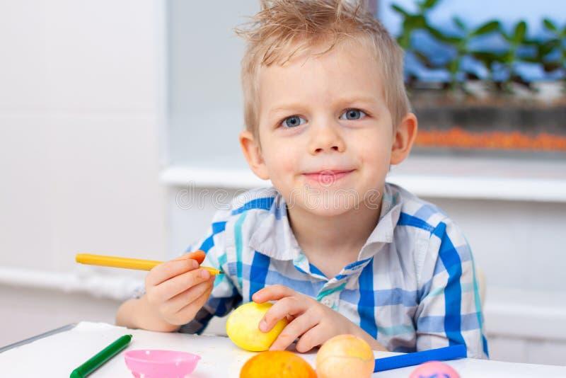 Den lilla blonda pojken förbereder sig för påsk och målar ägg färgrika markörer Påsk- och feriebegrepp arkivfoton