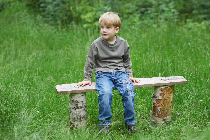Den lilla blonda pojken i jeans som sitter p?, parkerar b?nken arkivbilder