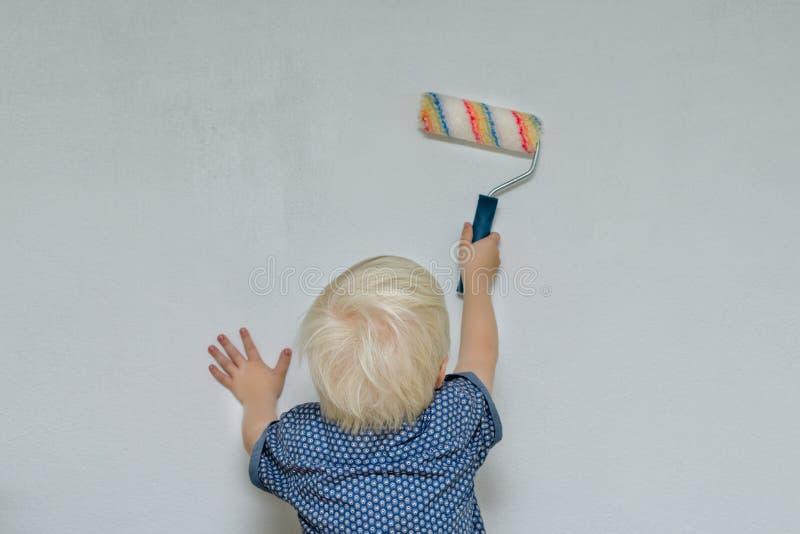 Den lilla blonda pojken målar en vägg med en rulle tillbaka sikt fotografering för bildbyråer