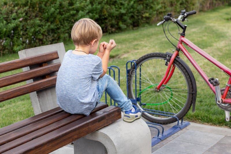 Den lilla blonda upprivna pojken i tillfällig jeans bär bara att sitta på träbänk parkerar in Ensam olycklig unge utomhus royaltyfria foton