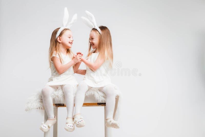 Den lilla blondinen kopplar samman i vita klänningar med kaninöron Studiofoto på grå bakgrund Ungar firar påsk royaltyfri fotografi