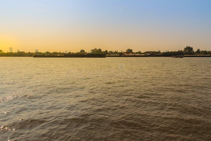Den lilla bogserbåten drar en stor sändningspråm upp Chao Phra royaltyfri foto