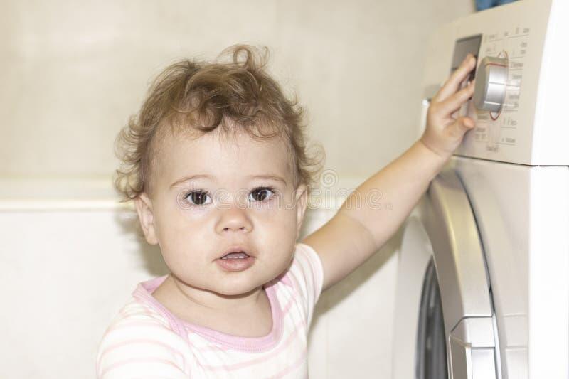 Den lilla Caucasian flickahuligan trycker på knappen av en tvättmaskin royaltyfria bilder