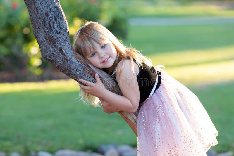 Den lilla Caucasian flickan i festlig klänning på en trädfrunch som är bakbelyst med solen i, parkerar royaltyfri foto