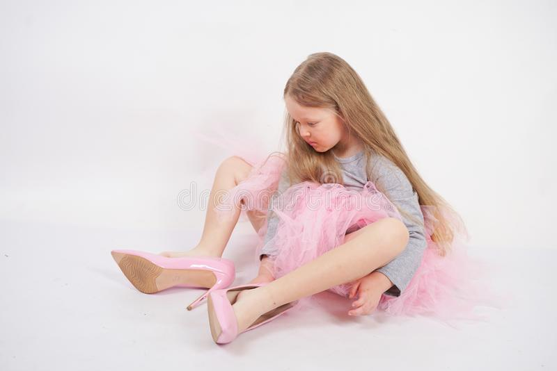 Den lilla caucasian flickan med långt blont hår sitter i grå t-skjorta och rosa pösig kjol på vit studiobakgrund bara arkivfoto