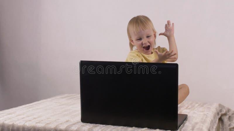 Den lilla caucasian flickan ser in i datorbärbara datorn och applåderar hennes händer royaltyfria foton