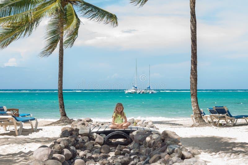 Den lilla Caucasian flickan sitter på stranden Blå himmel, gömma i handflatan, och havet är som en bakgrund royaltyfri fotografi
