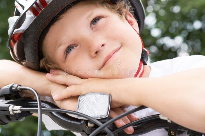 Den lilla Caucasian pojkecyklisten i skyddande hjälm satte hans huvud på styret av cykeln som poserar för kameran en pojke arkivbilder