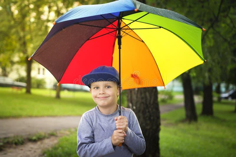 Den lilla caucasian pojken med det färgrika paraplyet parkerar in efter regn på solig sommardag royaltyfria foton
