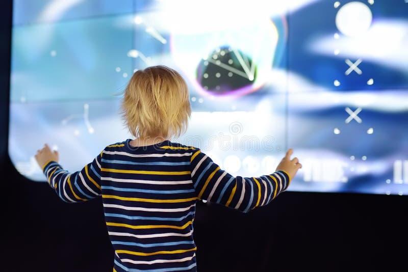 Den lilla caucasian pojken ser en utläggning i ett vetenskapligt museum fotografering för bildbyråer