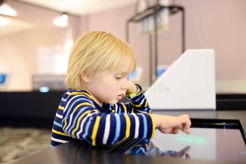 Den lilla caucasian pojken ser en utläggning i ett vetenskapligt museum arkivbilder