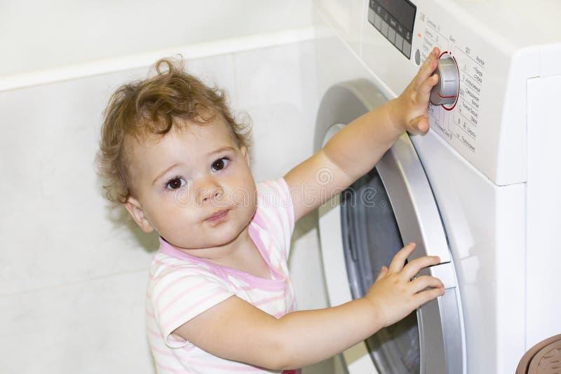 Den lilla caucasianen behandla som ett barn flickan som 1 år vänder knappen av tvättmaskinen royaltyfri foto