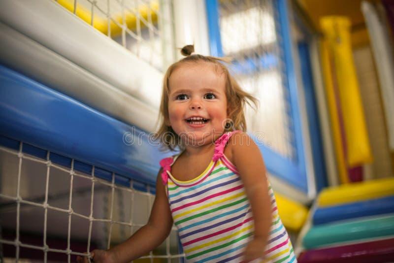 Den lilla caucasianen behandla som ett barn i lekplats Den lilla flickan klättrar upp sten royaltyfri foto