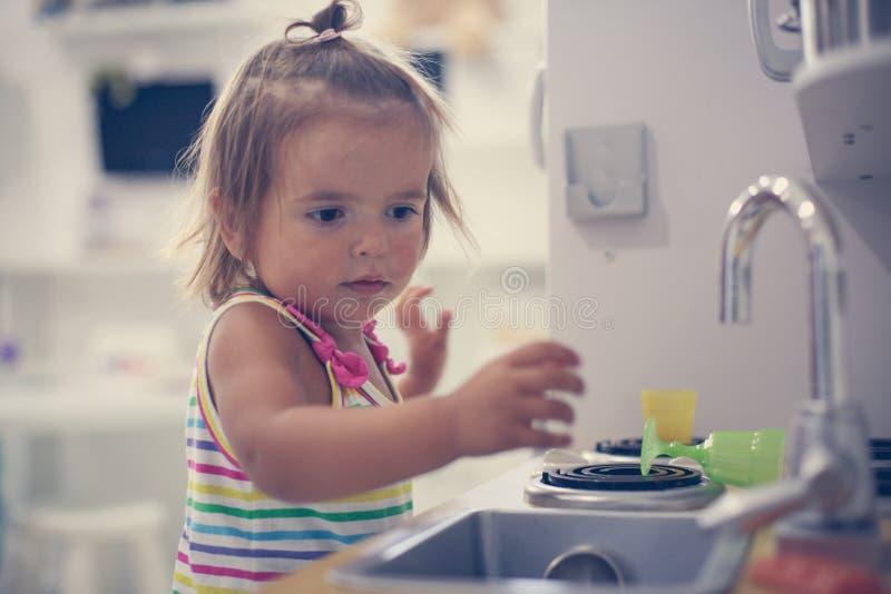 Den lilla caucasianen behandla som ett barn i lekplats Liten flicka som spelar med till royaltyfri fotografi