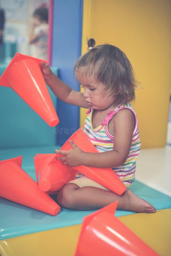 Den lilla caucasianen behandla som ett barn i lekplats Liten flicka som spelar med till royaltyfri bild