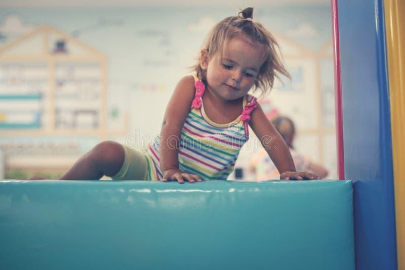 Den lilla caucasianen behandla som ett barn i lekplats Lyckliga små behandla som ett barn klättring royaltyfria foton