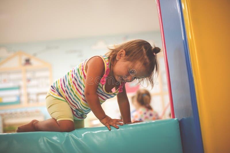 Den lilla caucasianen behandla som ett barn i lekplats Lyckliga små behandla som ett barn klättring royaltyfri fotografi