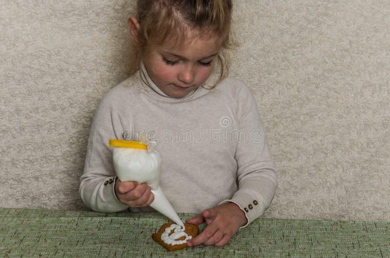 Den lilla charmiga flickan dekorerar det nya årets pepparkaka med isläggning för vitt socker royaltyfria foton