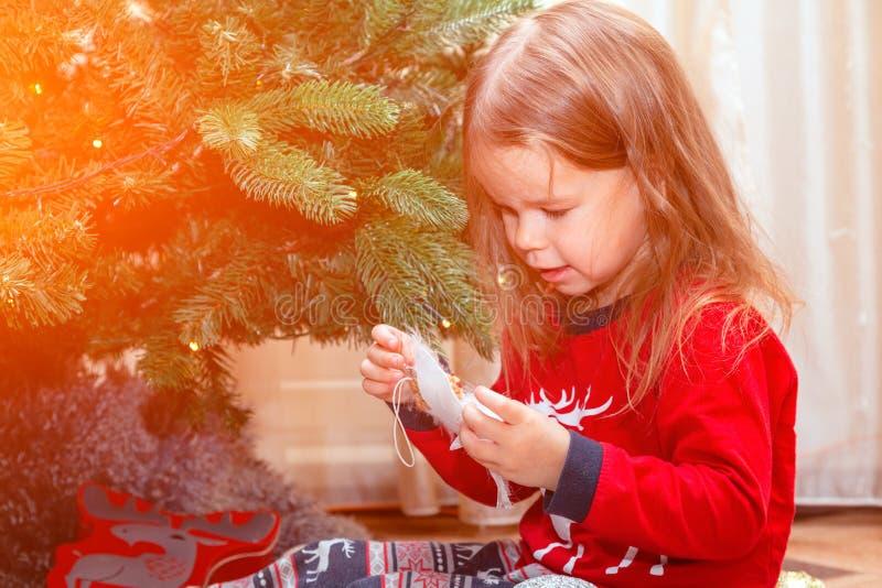 Den lilla charmiga flickan i pyjamas hjälper henne föräldrar att dekorera julgranen tidigt på morgonen, undersöker leksaken arkivfoton