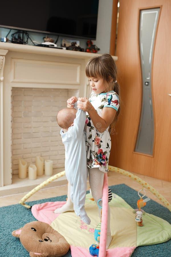 Den lilla charmiga flickan rymmer hennes mycket lilla broder på mattan på golvet i rummet arkivfoton