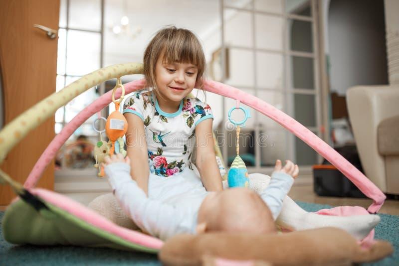 Den lilla charmiga flickan ser hennes mycket lilla broder som ligger på mattan på golvet i rummet arkivbild