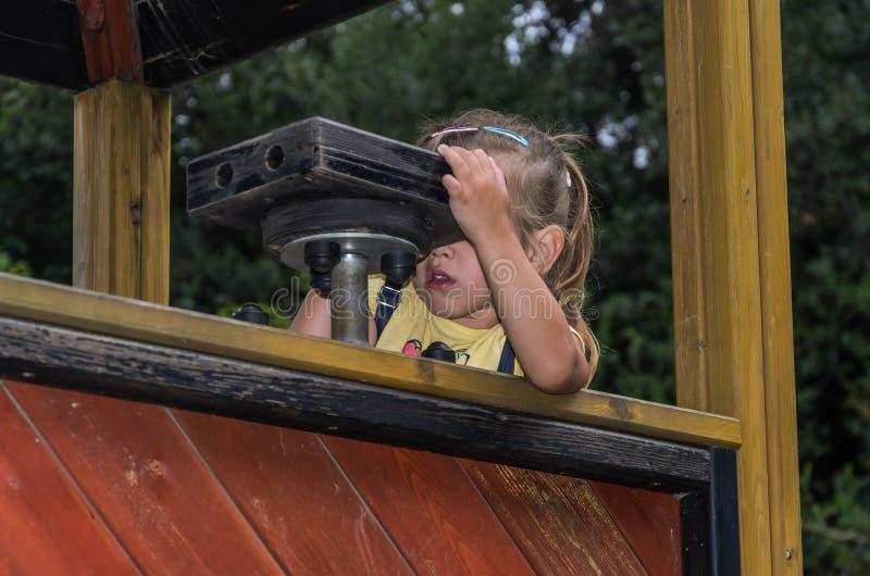 Den lilla charmiga flickan ser till och med leksakkikaren på lekplatsen arkivfoto