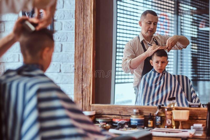 Den lilla charmiga pojken f?r moderiktig frisyr fr?n mogen fris?r p? den trendiga friseringsalongen royaltyfri fotografi