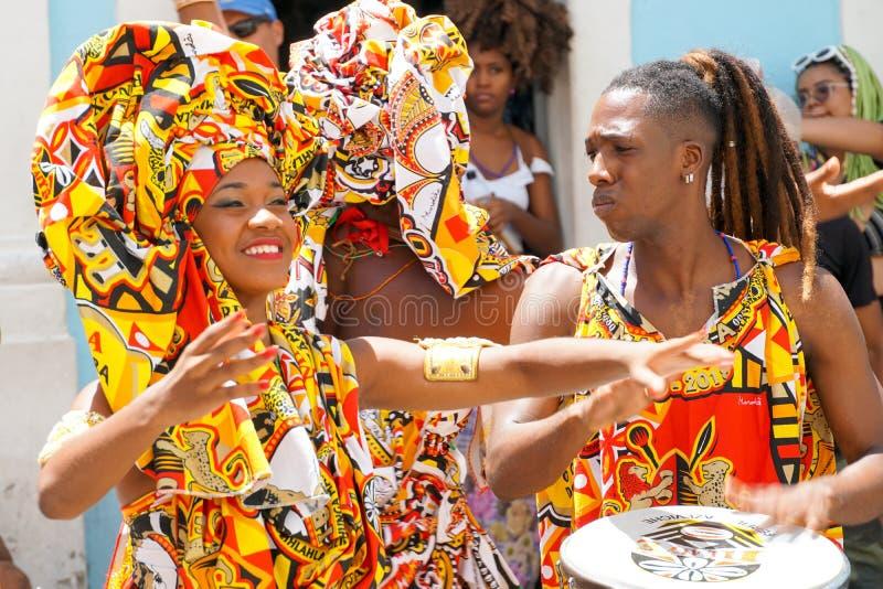 Den lilla dansaren ståtar med traditionella dräkter och instrument som firar med rumlare karnevalet, Brasilien arkivfoto