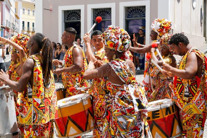 Den lilla dansaren ståtar med traditionella dräkter och instrument som firar med rumlare karnevalet, Brasilien royaltyfria bilder
