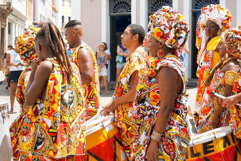 Den lilla dansaren ståtar med traditionella dräkter och instrument som firar med rumlare karnevalet, Brasilien royaltyfri bild