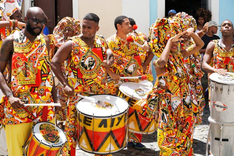 Den lilla dansaren ståtar med traditionella dräkter och instrument som firar med rumlare karnevalet, Brasilien arkivfoton