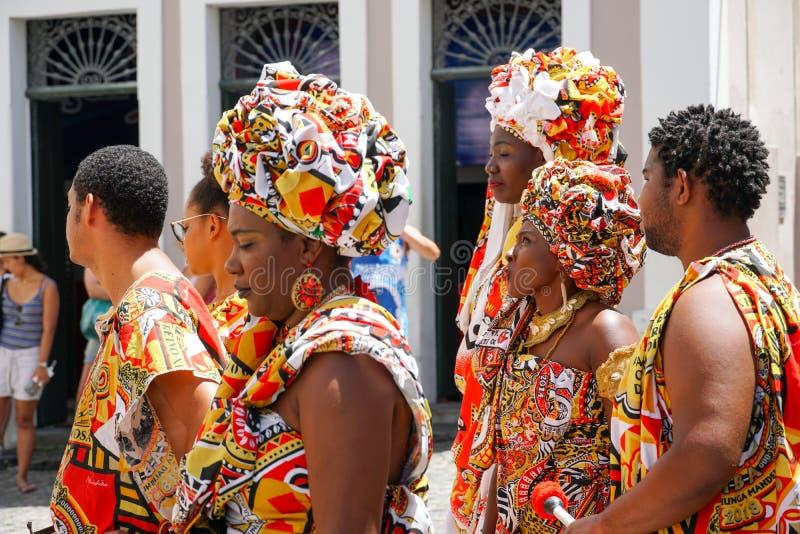 Den lilla dansaren ståtar med traditionella dräkter och instrument som firar med rumlare karnevalet, Brasilien royaltyfri fotografi