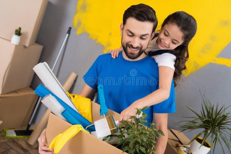 Den lilla dottern med målarpenselkramar avlar, som håller asken av hjälpmedel och saker royaltyfria foton