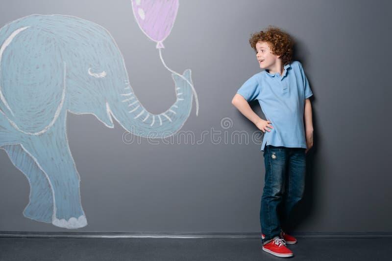 Den lilla elefanten ger en ballong arkivfoton