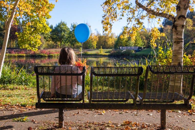 Den lilla ensamma flickan med en blå ballong och en grupp av sidor för en nedgång sitter på en tom bänk i en nedgång parker royaltyfri foto