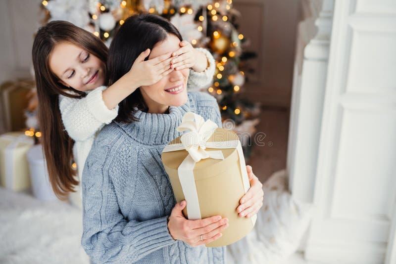 Den lilla förtjusande kvinnliga ungen förbereder överraskningen för hennes moder, clos royaltyfria bilder
