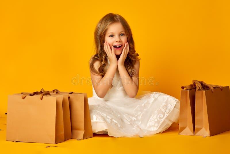 Den lilla förvånade flickan rymmer påsar på gul bakgrund arkivfoto