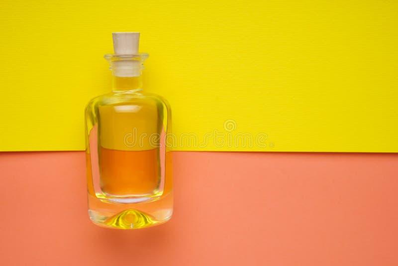 Den lilla flaskan av solros-kärnar ur olja på den gula lägenheten royaltyfria foton
